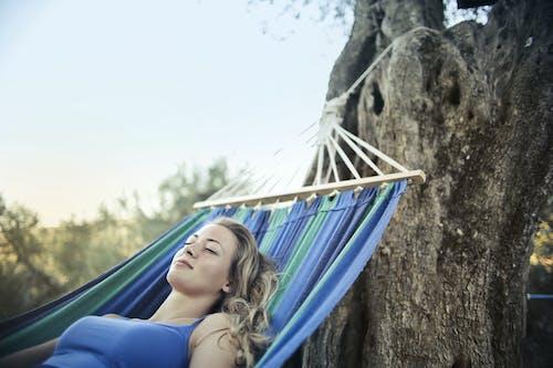 Photo of Woman in Blue Spaghetti Strap Top Sleeping on a Blue Hammock