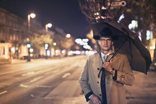 Selective Focus Photo of Man in Black Hat and Brown Overcoat Holding a Umbrella While Walking on the Sidewalk