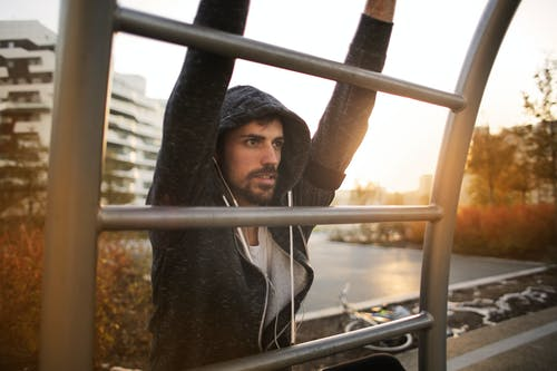 Young athletic male in sportswear with earphones doing exercises on ladder while training on sport ground near river in autumn morning in city