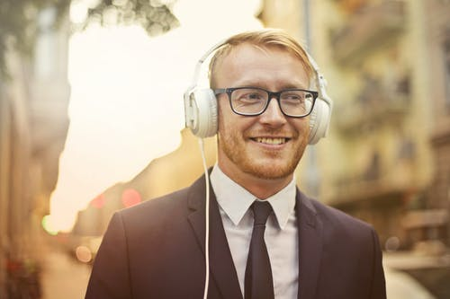 Selective Focus Photo of Smiling Man in a Black Suit and Black Framed Eyeglasses Listening to Music on White Headphones