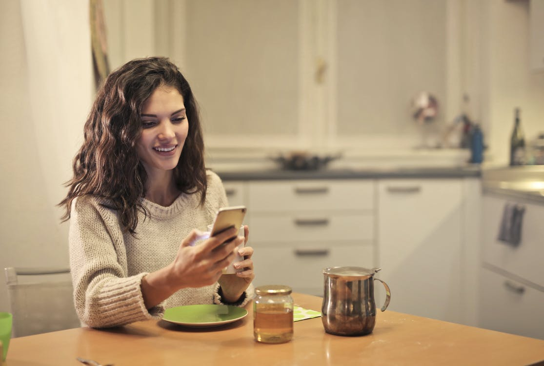 Young woman drinking tea and using smartphone