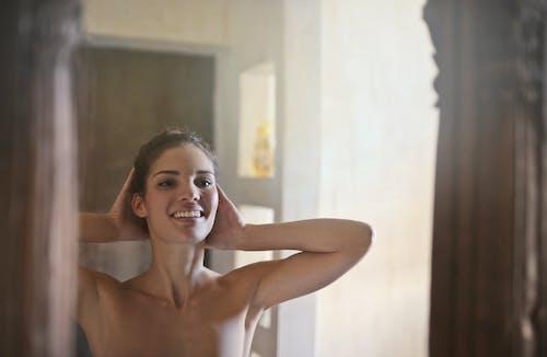 看鏡子的愉快的婦女在衛生間裡