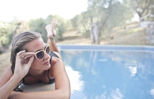 Selective Focus Close-up Photo of Woman in a Black Bikini Lying Down Poolside Posing in Sunglasses