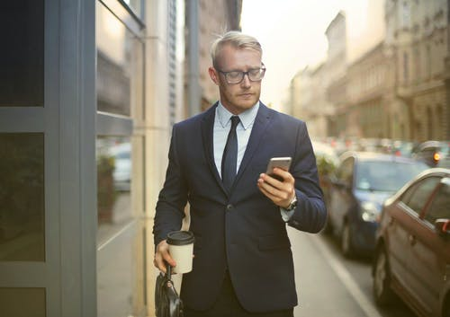 Selective Focus Photo of Walking Man in Black Suit Carrying a To Go Cup and Briefcase While Using His Phone
