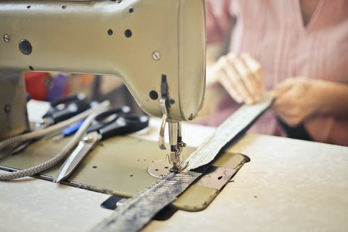 Crop craftswoman in casual wear sitting at old fashioned sewing machine and stitching pieces of fabric while working in workshop