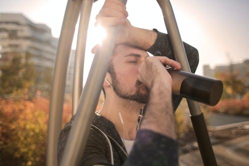 在大街上訓練期間累的運動員人喝水