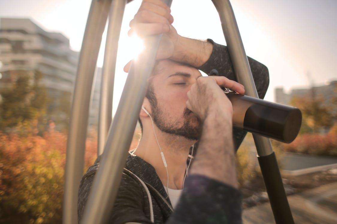 Tired sportsman man drinking water during training on street