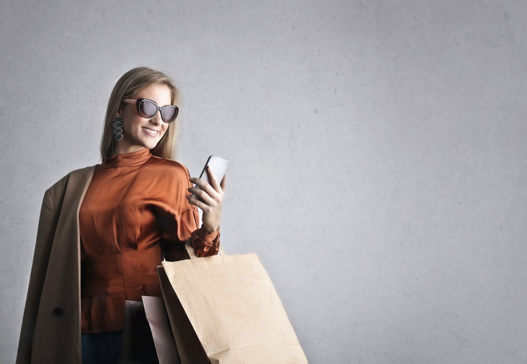 Smiling female in trendy wear and stylish sunglasses standing with paper shopping bags on background of gray wall and browsing mobile phone