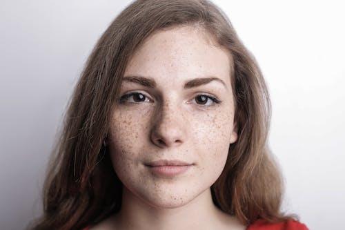 Photo En Gros Plan D'une Femme Aux Taches De Rousseur En Haut Rouge Devant Fond Blanc