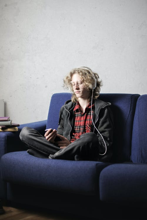 Photo of Person In Black Hoodie With Headphones on  Sitting on Blue Sofa