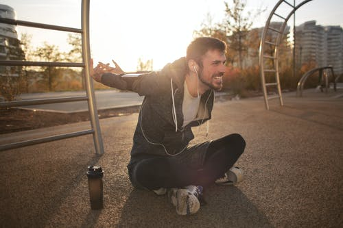 Cheerful athletic man stretching arms on sports ground