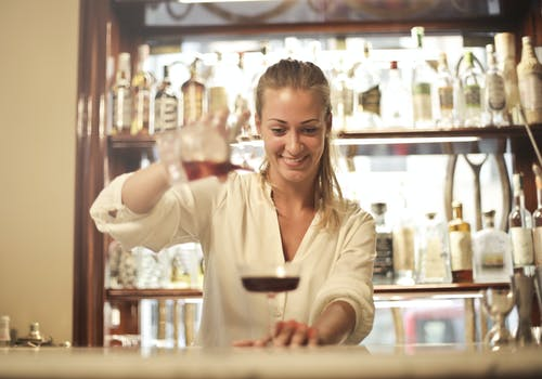 Cheerful female bartender pouring cocktail in bar