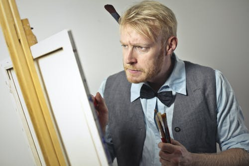 Concentrated male artist painting on canvas in studio