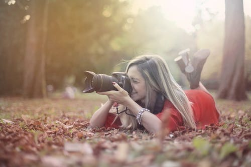 Smiling woman taking photos on professional photo camera in forest