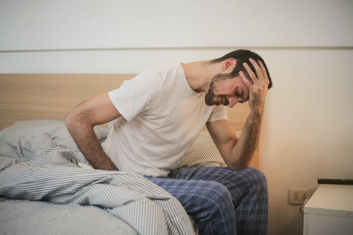 Young man in sleepwear suffering from headache in morning