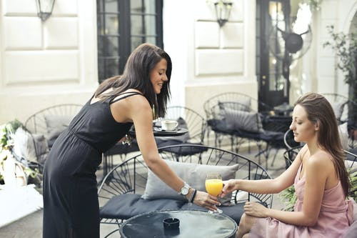 Side view of young female in summer outfit standing with tray near table in outdoors cafe and passing glass of fresh juice to friend while relaxing together in city