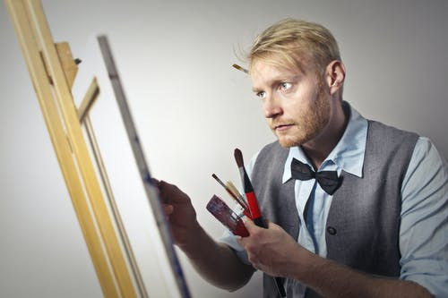 Calm male artist painting on canvas using paintbrushes