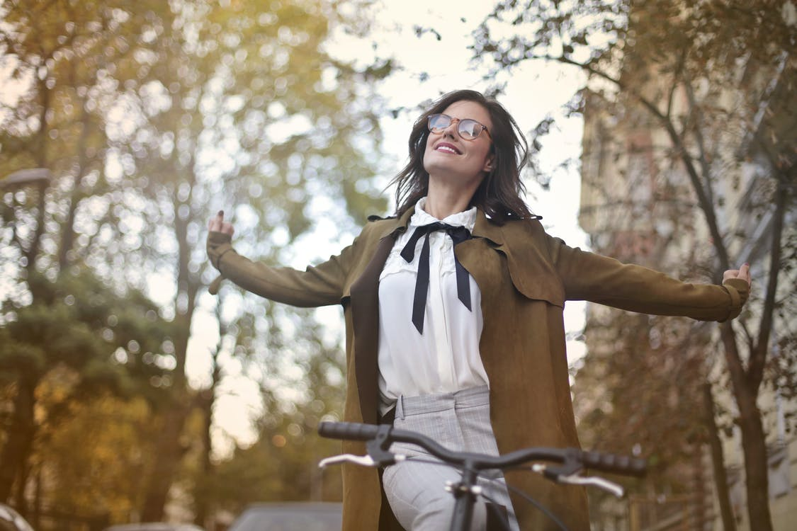Content woman in retro clothes on bicycle in street