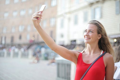 Selective Focus Photo of Smiling Woman in Red Tank Top Taking a Selfie