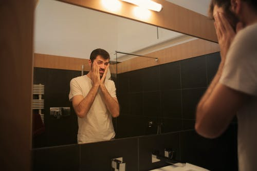 Tired man looking in mirror in bathroom