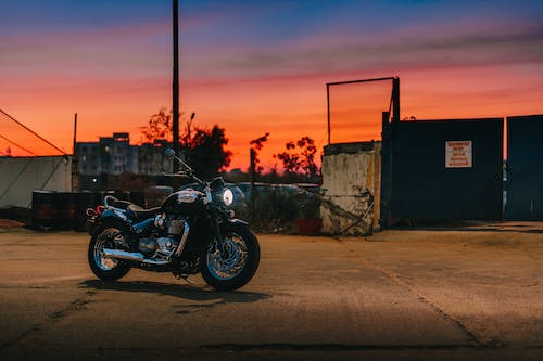 Black Motorcycle Parked Beside Fence during Sunset