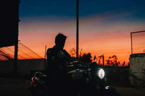 Silhouette of Man Riding Motorcycle during Sunset