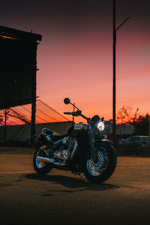 Black Motorcycle Parked Beside Black Metal Post during Sunset