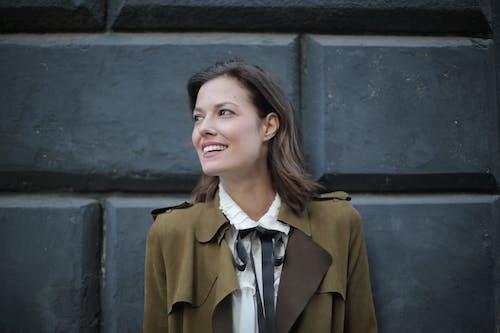 Stylish cheerful woman in coat on street