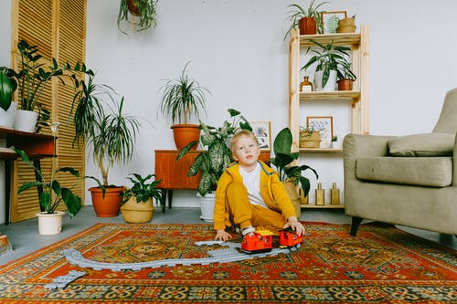 Playful child in casual wear sitting on carpet in cozy living room and playing with plastic railway and train while having fun during weekend