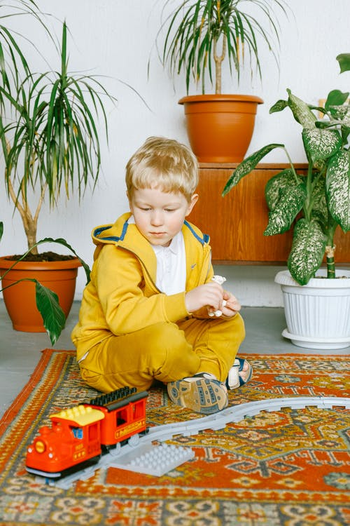 Curious kid in casual clothes sitting on floor of cozy living room at home and playing with plastic train and railway