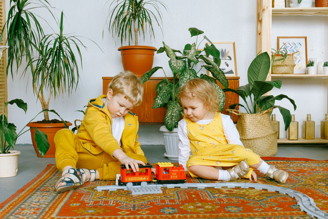 Adorable little boy and girl playing with toy train