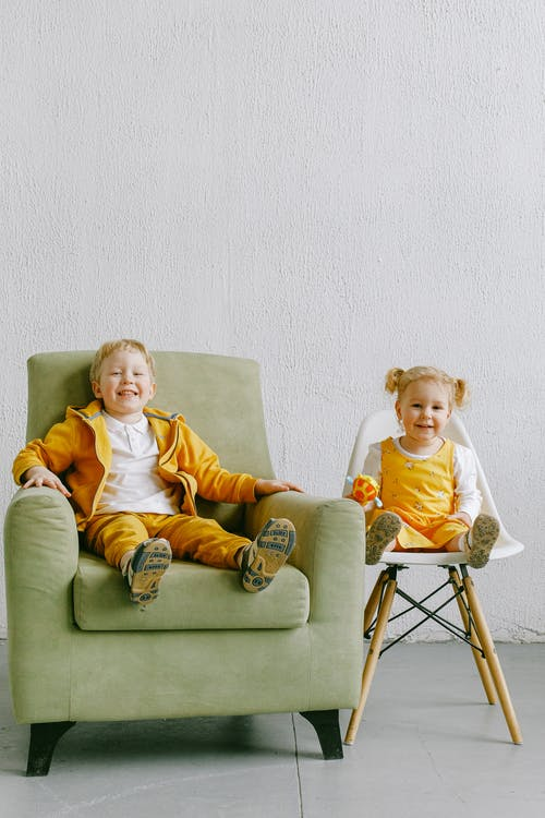 Adorable boy and girl in casual clothing relaxing in armchair and on chair in living room while smiling and looking at camera