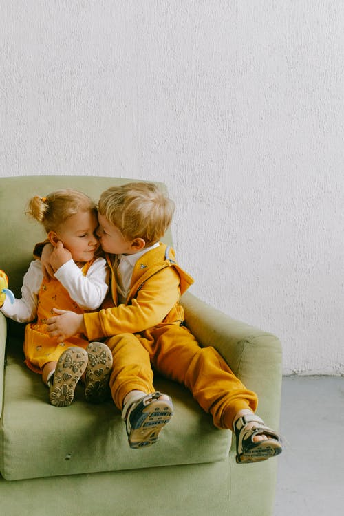 Little brother and sister in casual wear sitting in cozy armchair together and hugging in living room
