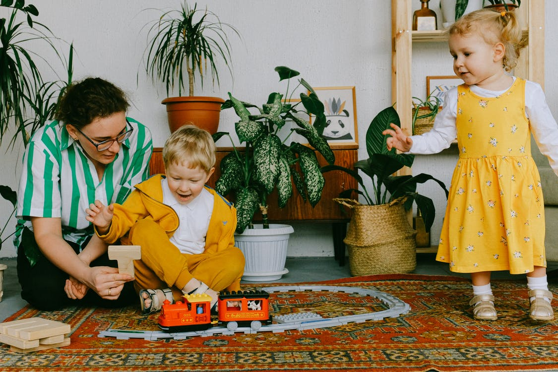 Mom and adorable little brother and sister in casual wear gathering in cozy living room during weekend and having fun together while playing with plastic railway