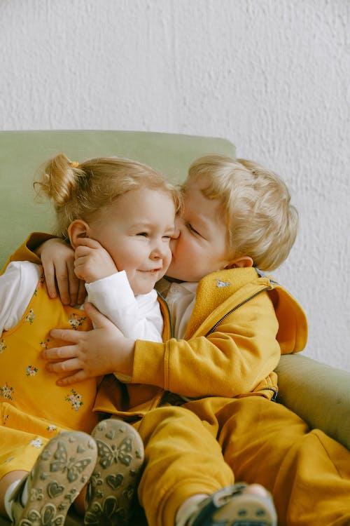 自宅の肘掛け椅子で抱き締める陽気な小さな兄弟