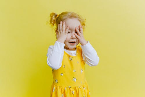 Photo of Young Girl in White Long Sleeve Top and Yellow Dress Covering Her Face With Her Hands