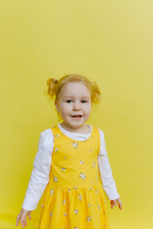 Adorable Girl Standing Beside Yellow Wall