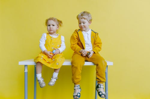 Siblings Sitting On A White Table