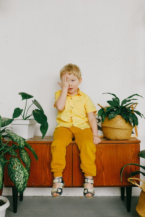 Boy in Yellow Polo Shirt Sitting on Brown Wooden Table