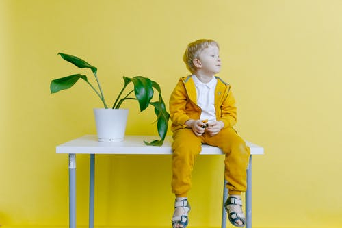 Boy in Yellow Jacket and Yellow Pants Sitting on White Table