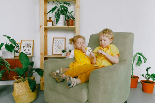 A Photo Of Siblings Eating Grapes