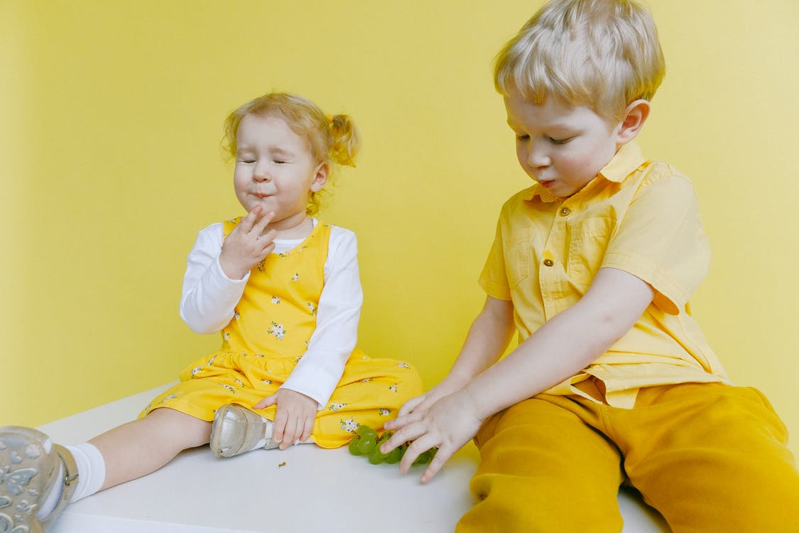 Toddlers Sitting On White Table While Eating Green Grapes