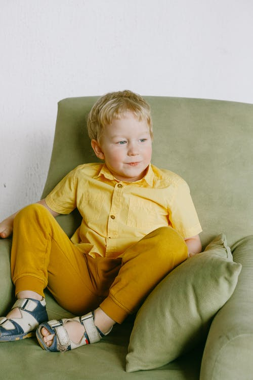 Boy in Yellow Button Up Shirt Sitting on Gray Sofa Chair