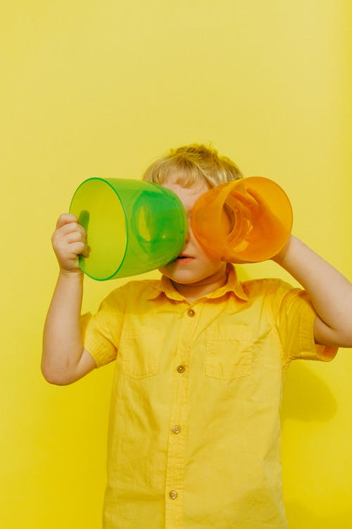 Boy in Yellow Button Up Shirt Holding Yellow and Green Plastic Containers