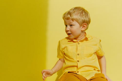 Child in Yellow Button Up Shirt Sitting Near Wall