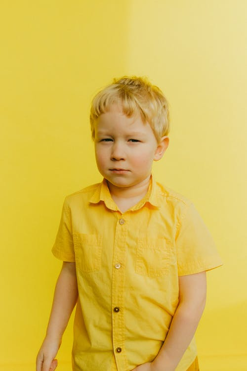 Boy in Yellow Button Up Shirt Standing Near Wall