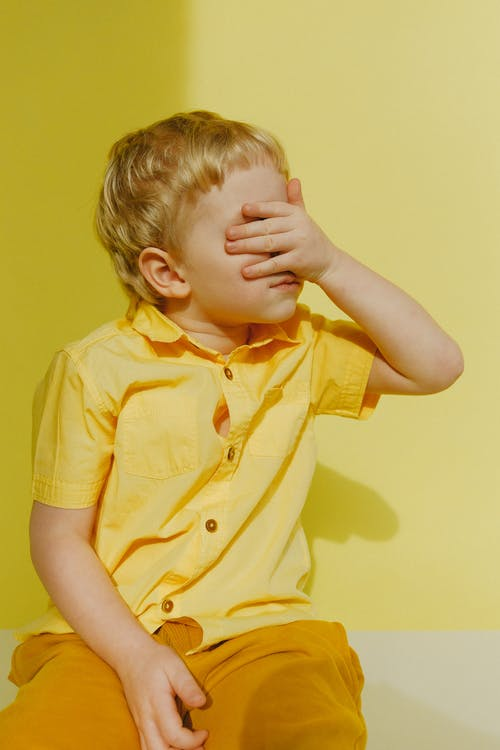 Photo Of A Boy Covering His Eyes
