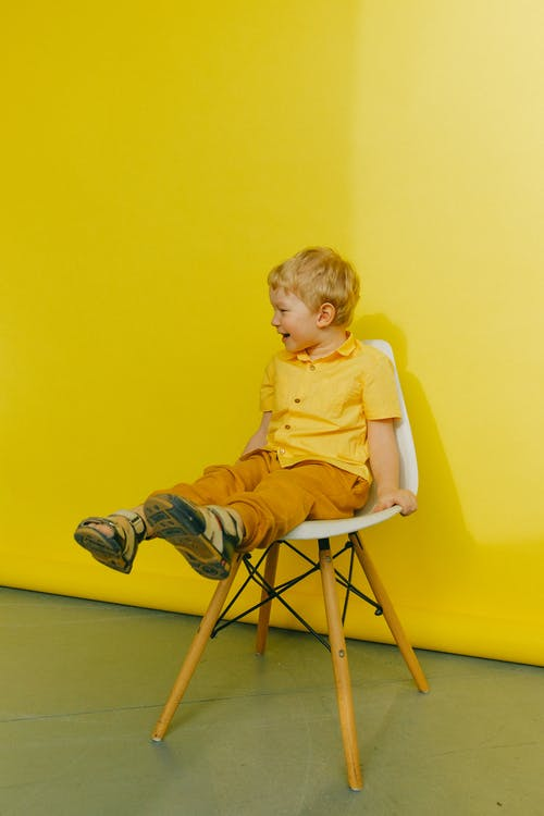 Boy in Yellow Polo Shirt Sitting on  Chair Near Wall