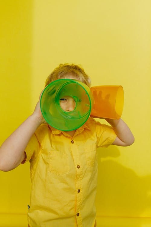 Boy in Yellow Button Up Shirt Holding Green  and Orange Plastic Container