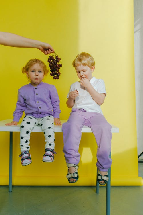 Person Holding Grapes Between Children Sitting on Table